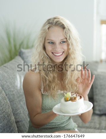 Happy woman gesturing while holding cake in house - stock photo