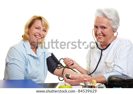 Happy woman getting blood pressure measure at health check - stock photo