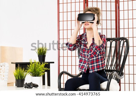 Happy woman getting experience using VR-headset glasses of virtual reality at home much gesticulating hands - stock photo