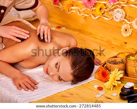 Happy woman getting stone therapy massage in gerbera spa. - stock photo