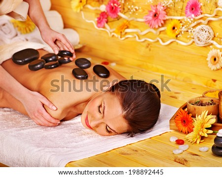 Happy woman getting stone therapy massage in spa.