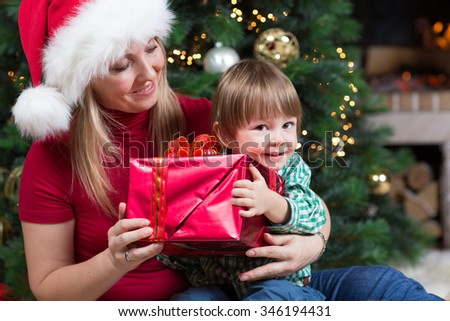Happy woman gives wrapped christmas presents gifts to infant child baby toddler sitting near Christmas tree - stock photo