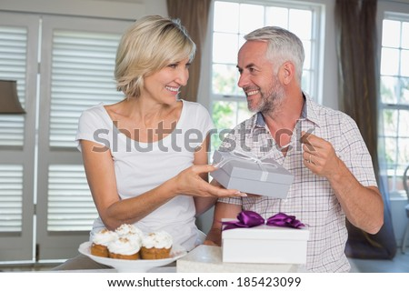 Happy woman giving a gift box to smiling mature man at home - stock photo