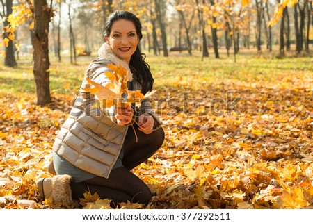 Happy woman giving autumn leaves in park - stock photo