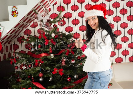 Happy woman giving thumbs up in front of Christmas natural tree  - stock photo