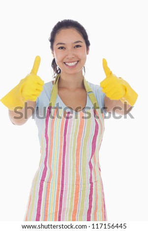 Happy woman giving thumbs up in rubber gloves and apron - stock photo