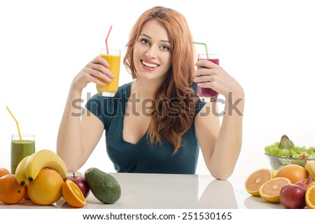 Happy woman having a table full of organic food,juices and smoothie. Cheerful young woman eating healthy salad and fruits. Isolated on white - stock photo