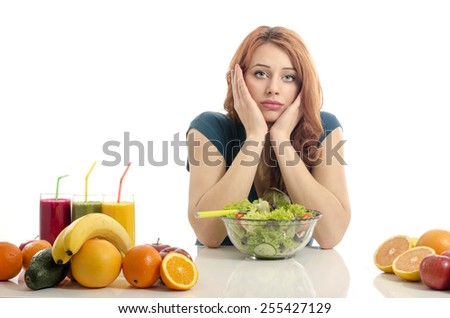 Happy woman having a table full of organic food,juices and smoothie. Cheerful young woman eating healthy salad and fruits. Isolated on white. - stock photo