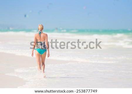 Happy woman having fun, enjoying summer, walking joyfully on tropical beach. Beautiful caucasian model  wearing colorful scarf and turquoise bikini on vacations on Paje beach, Zanzibar, Tanzania - stock photo