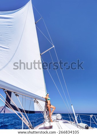 Happy woman having fun on sailboat, enjoying active summer vacation, luxury water transport, relaxation and enjoyment concept - stock photo