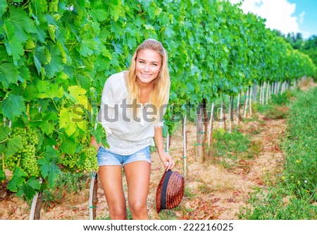 Happy woman having fun on vineyard, enjoying fresh ripe grapes, autumn harvest season, agriculture and farming concept - stock photo
