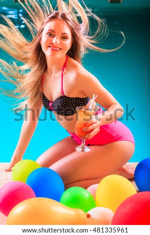 Happy woman having fun with balloons and cocktail drink alcohol. Pretty attractive girl relaxing at swimming pool edge poolside.