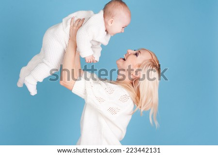 Happy woman having fun with her newborn child over blue. Wearing winter knitted clothes