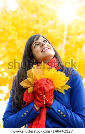 Happy woman having fun with leaves on autumn sunshine day in park. Beautiful girl smiling and looking up towards copy space with fall golden trees and sun. - stock photo
