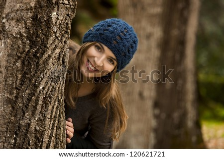 Happy woman hiding behind a tree in a beautiful autumn day - stock photo