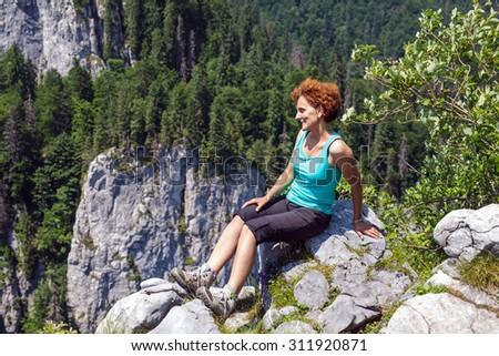 Happy woman hiker sitting on the mountain peak - stock photo