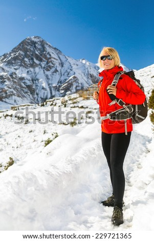 Happy woman hiker trekker nordic walking in Himalaya Mountains in Nepal. Trekking on snow white winter nature, beautiful mountain landscape. Fitness and adventure explore achievement outdoors. - stock photo