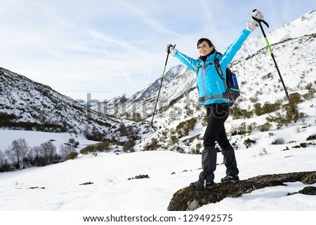 Happy woman hiking on winter snowy mountain trip with arms up.  Successful hiker travel achievement. - stock photo