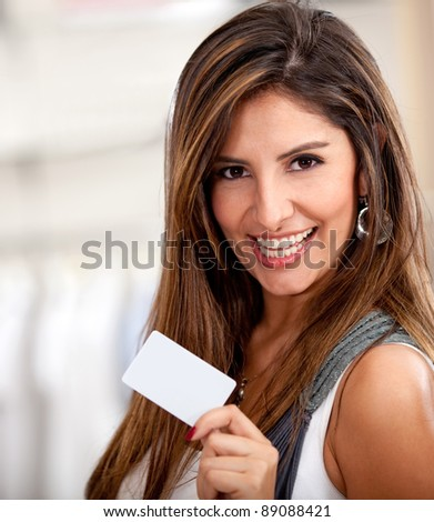 Happy woman holding a credit or debit card and smiling - stock photo