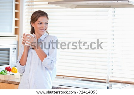 Happy woman holding a cup of coffee in her kitchen - stock photo