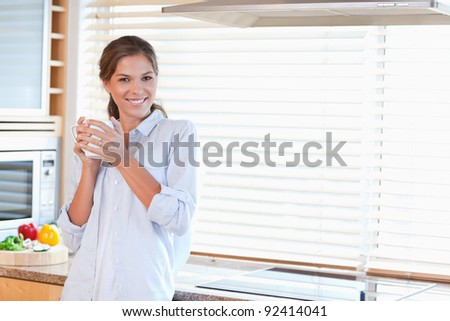 Happy woman holding a cup of tea in her kitchen - stock photo
