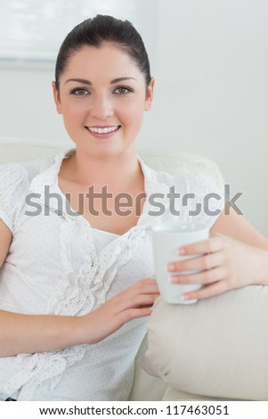 Happy woman holding a cup while sitting on a couch in a living room and relaxing