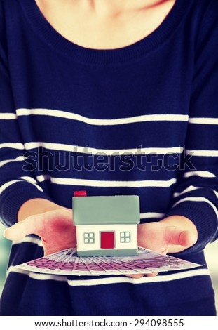 Happy woman holding a house model - stock photo