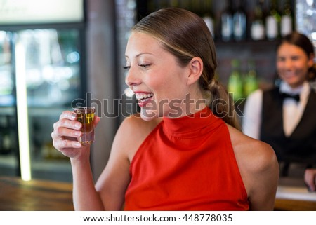 Happy woman holding a tequila shot in front of bar counter in bar