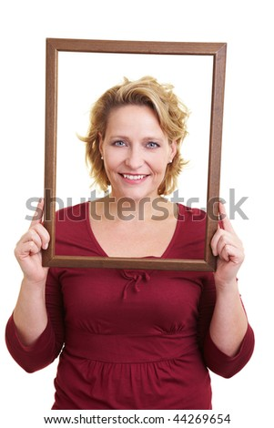 Happy woman holding a wooden frame in front of her face - stock photo