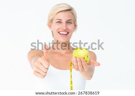 Happy woman holding an apple with thumbs up on white background - stock photo