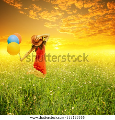 Happy woman holding balloons and jumping on flower  grass field and sunset.holiday vacation concept. - stock photo