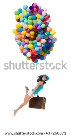 Happy woman holding balloons and old suitcase, isolated on white background. Concept of travel and freedom - stock photo