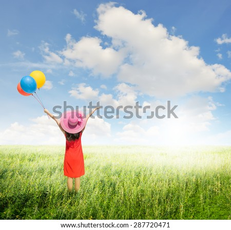 Happy Woman holding balloons  in green grass fields with clouds sky.Summer holiday concept. - stock photo