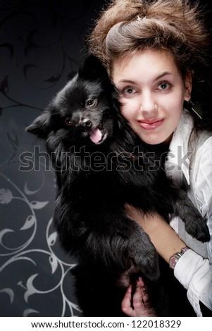 Happy woman holding black dog - stock photo
