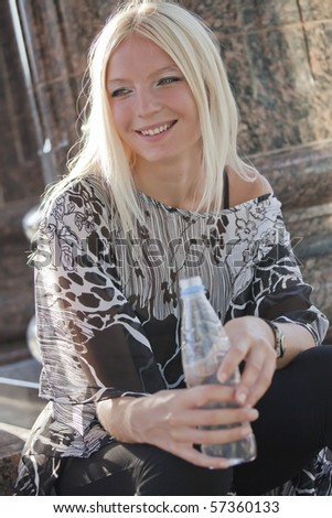 happy woman holding bottle of water outdoors