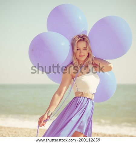 Happy woman holding bunch of  air balloons at the beach. Photo with instagram style filters - stock photo