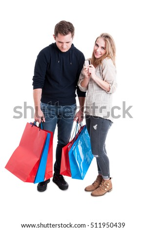 Happy woman holding credit card and sad man carrying bunch of shopping bags  isolated on white background