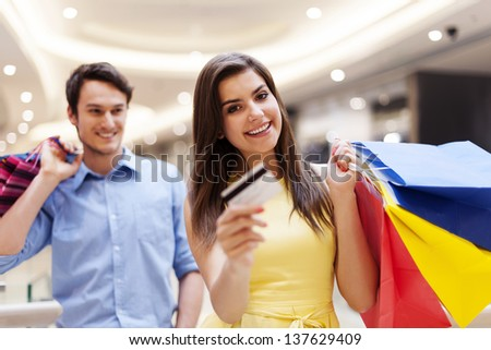 Happy woman holding credit card and shopping bags  - stock photo