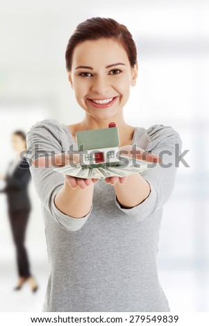 Happy woman holding dollar banknotes and house. - stock photo