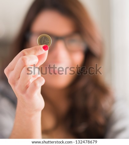 Happy Woman Holding Euro Coin, Indoors - stock photo