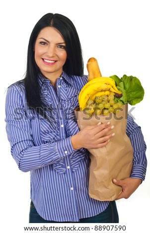 Happy woman holding full paper shopping bag with food isolated on white background