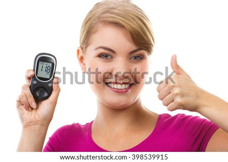 Happy woman holding glucose meter with positive result of measurement sugar level and showing thumbs up, concept of diabetes, checking sugar level