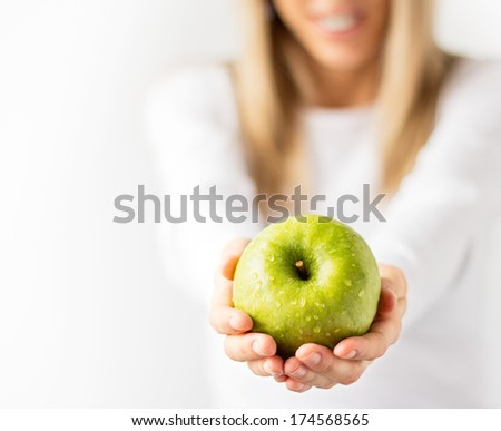 Happy woman holding green apple in both hands. Healthy life, diet and nutrition concept. - stock photo