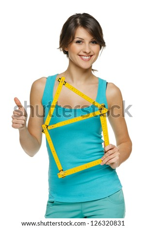 Happy woman holding home frame and showing thumb up sign, over white background - stock photo