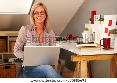 Happy woman holding laptop computer on lap, sitting at home, smiling, looking at camera. - stock photo