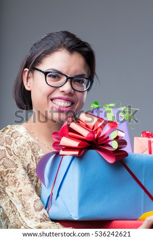 happy woman holding lots of gifts and packets