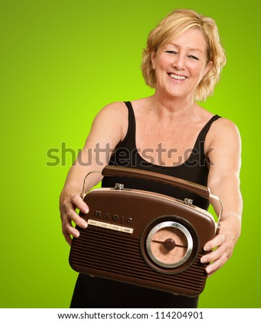 Happy Woman Holding Old Radio Isolated On Green Background - stock photo