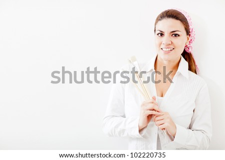Happy woman holding painting brushes - over a white background - stock photo
