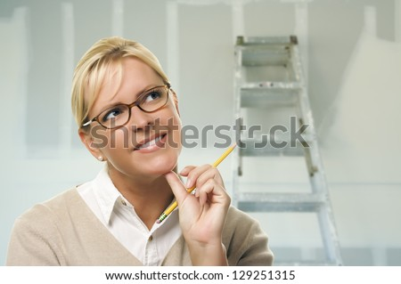 Happy Woman Holding Pencil Inside Room with New Sheetrock Drywall and Ladder. - stock photo