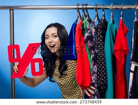 Happy Woman Holding Percent Sign At The Clothing Rack With Dresses On Blue Background - stock photo